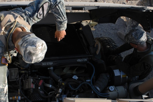 Two Soldiers from the A Co. 115th Brigade Support Battalion, 1st Brigade Combat Team, 1st Cavalry division, inspect the wiring and hoses of their issued vehicle at the National Training Center Oct. 4 on Fort Irwin, Calif.