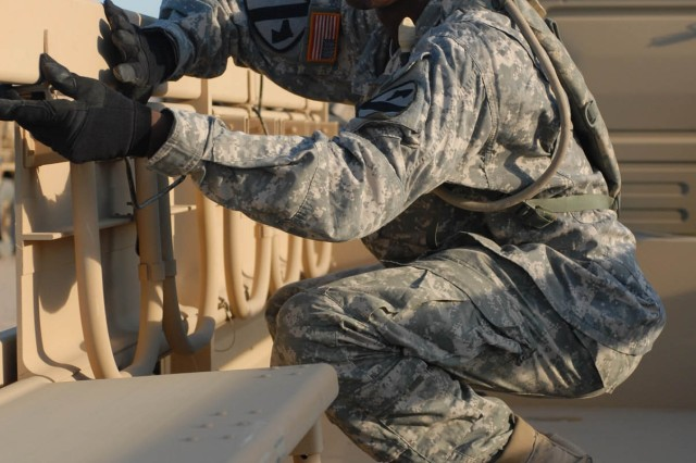 Spc. Mitchell Alphonso Page, Mechanic (63C), Headquarters and Headquarters Company, 115th Brigade Support Battalion, 1st Cavalry Division, who is a native of Portsmouth, Va., Inspects the 'Troop Seats' on an LMTV for serviceability during the 1st Brigade Combat Team's vehicle draw Oct. 4 at the National Training Center on Fort Irwin, Calif.