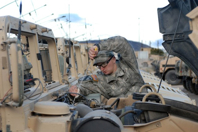 "San Diego native Pfc. Jared Smith, forward observer, conducts Preventative Maintenance Checks and Services for his humvee assigned during a vehicle draw Oct. 4 at the National Training Center (NTC) on Fort Irwin, Calif. The checks these ""Ironhorse"" Soldiers will conduct over the next two days are necessary to make sure these vehicles are operable to assist in the training here at NTC."