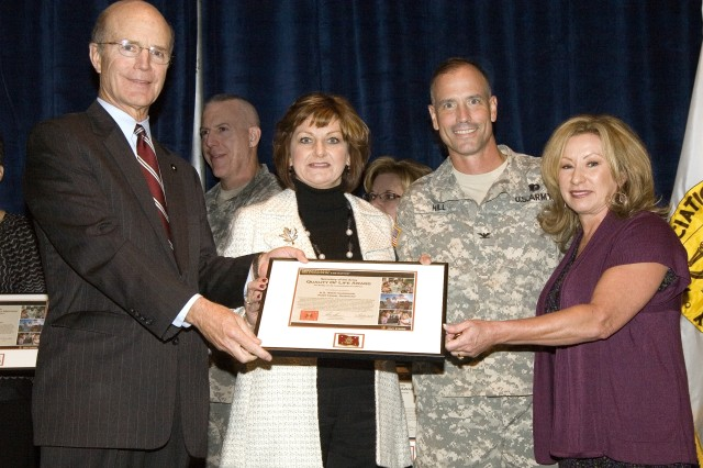 Col. Bill Hill, garrison commander, U.S. Army Garrison, Fort Hood; Sara Lynch, spouse of commanding general, 3rd corps; and Beth Ciotola, spouse of the command sergeant major, 3rd corps, accept the Quality of Life Award for Communications Excellence on behalf of Fort Hood. Secretary of the Army Pete Geren (left) presented the awards Oct. 7 at the 2008 Association of the United States Army Annual Meeting in Washington, D.C.