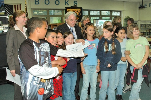 Professor Dieter Weirich, senior vice president of Corporate Communications for the Frankfurt Airport Services Worldwide, presents Aukamm Elementary School pupils at U.S. Army Garrison Wiesbaden, Germany, with a 2000-euro check for their joint Berlin Airlift video project with the German Grundschule Nauheim.