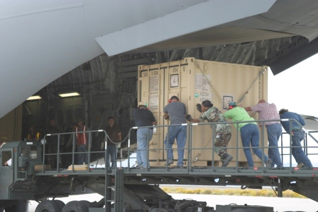 Employees loaded a C-17 Globemaster III with containers filled with components that make up an 800,000 gallon per minute Fuel System Supply Point module.
