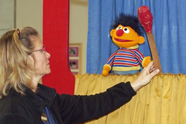 """Ernie,"" from Sesame Street fame, hands the match he and ""Bert"" found in the playground to Gertrud Medina, preschool room leader for the Landstuhl Child Development Center, during an Oct. 5 puppet show performed by the U.S. Army Garrison Kaiserslautern, Germany, Fire Department"