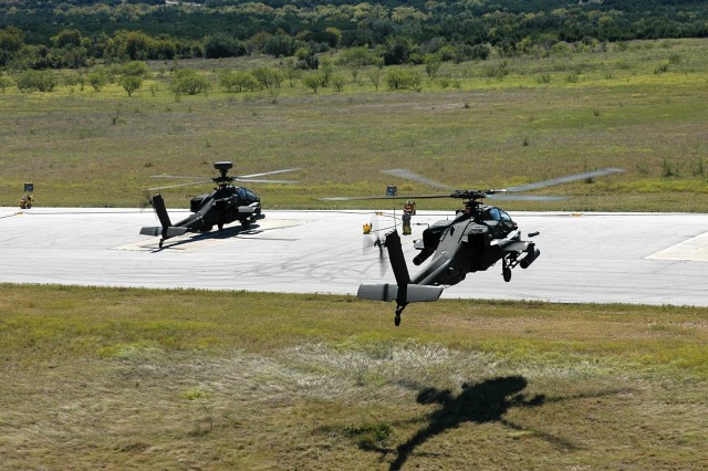"""After firing at the range during an aerial gunnery, an AH-64D Apache attack helicopter from the 4th """"Guns"""" Battalion, 227th Aviation Regiment, 1st Air Cavalry Brigade, 1st Cavalry Division, comes in for a landing at a Forward Arming and Refueling Point at Fort Hood, Texas, Oct 8. The FARP is where ammunition and fuel are kept so that the helicopters do not need to travel far when needing to rearm or refuel."""