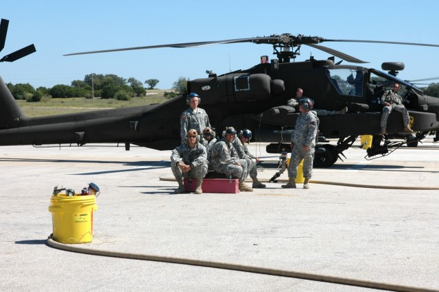 """A group of armament and fueling specialists from the 4th """"Guns"""" Battalion, 227th Aviation Regiment, 1st Air Cavalry Brigade, 1st Cavalry Division, hang out and wait for another aircraft to land at a Forward Arming and Refueling Point while some AH-64D Apache attack helicopter pilots wait their turn to fire during an aerial gunnery at Fort Hood, Texas, Oct. 8."""