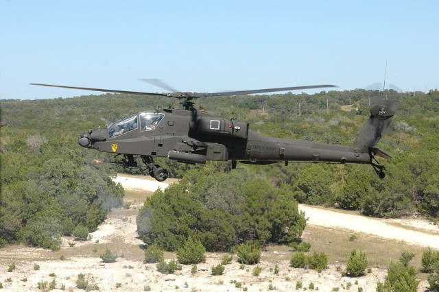 """An AH-64D Apache attack helicopter from the 4th """"Guns"""" Battalion, 227th Aviation Regiment, 1st Air Cavalry Brigade, 1st Cavalry Division, lets loose a stream of 30 mm rounds from its chain gun during an aerial gunnery at Fort Hood, Texas, Oct 8. The """"Guns"""" provide close air support and reconnaissance to ground troops when in combat. This training allows them to hone their skills for future operations."""