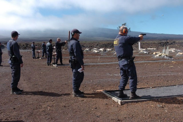 POHAKULOA TRAINING AREA, Hawaii - A 9 millimeter cartridge flies above a DA police officer's head as he, and other police officers, takes aim and shoot at range targets.