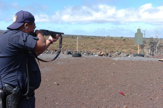 POHAKULOA TRAINING AREA, Hawaii - Sgt. Jay Tolentino, detachment training sergeant, fires a shotgun round as the 12-gauge cartridge discharges from the side.