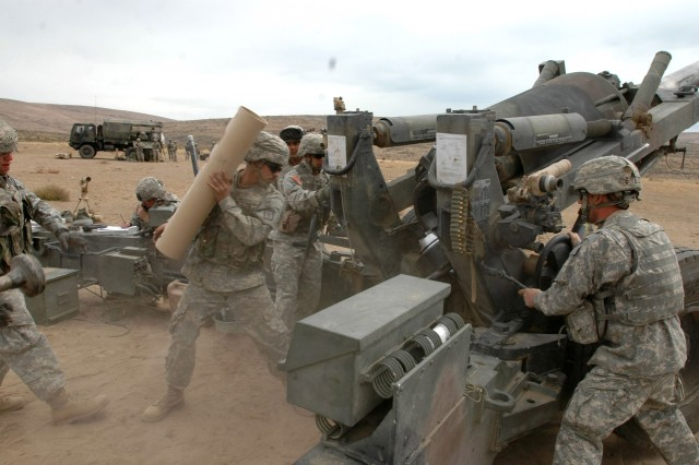 Soldiers from C Btry., 1-377th FA load a 155 mm round into an M198 howitzer during firing at Yakima Training Center.