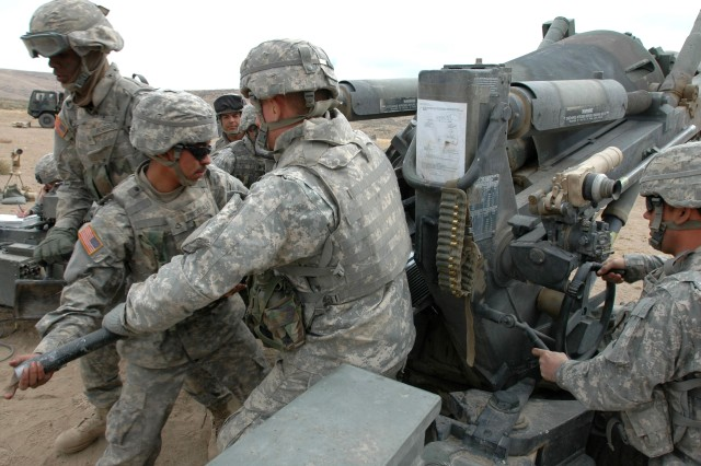 Soldiers with C Btry., 1-377 FA ram home a 155 mm round while firing in support of infantry at Yakima Training Center, Oct. 2.