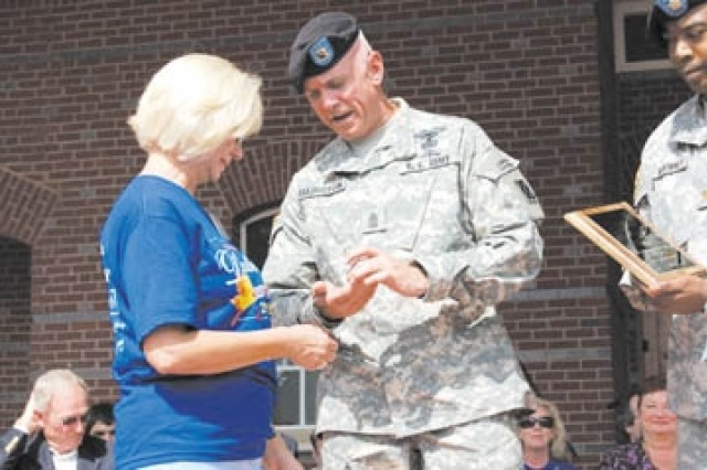 Sgt. Maj. Richard Hairston, senior noncommissioned officer of operations for the 2nd Bn., 69th Armor Regt., hands Angie Doerlich, Duluth (Ga.) First United Methodist Church, a battalion coin, Sept. 26 during a ceremony at the Duluth Fall Festival. Doerlich served as the military chairperson for the festival.