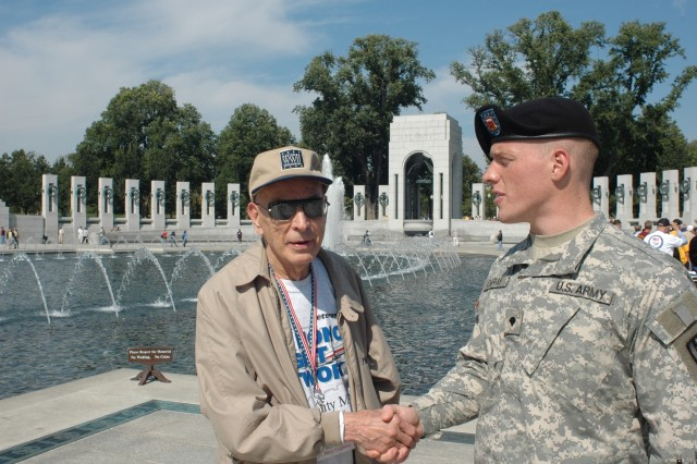 Soldier of the Year Spc. David Obray greets a veteran Wednesday at the World War II Memorial in Wahington, D.C.