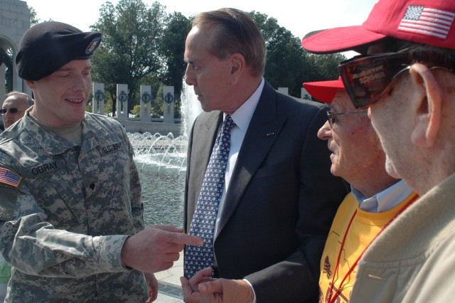 Former Senator Bob Dole and the Army's current Soldier of the Year Spc. David Obray talk with World War II veterans at the memorial built to honor those who fought more than 60 years ago.