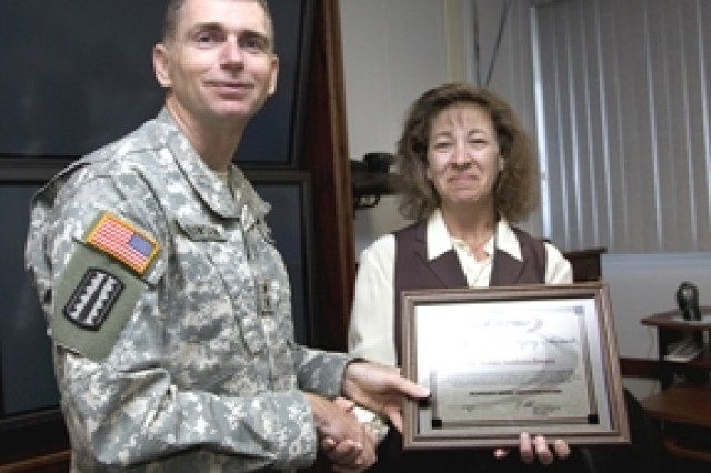 PICATINNY ARSENAL, N.J. -- Maj. Gen. Fred D. Robinson Jr. presents a certificate to Nolda Seidenschwarz that recognizes her accomplishments as the environmental and safety coordinator for ARDEC's Munitions Engineering and Technology Center here Oct.