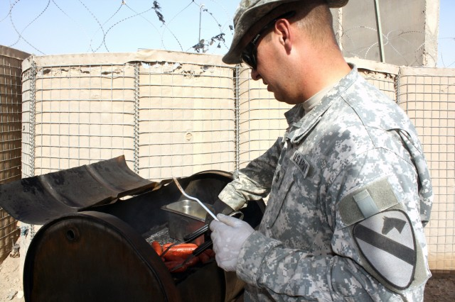 Sgt. 1st Class Joseph Brauchle, assigned to HHC, 27th BSB, 4th BCT, 1st Cav. Div., cooks sausages on the grill during a cookout at the COB Adder Visitor Control Center held for the Iraqi translators and workers to celebrate the end of Ramadan Oct. 4.