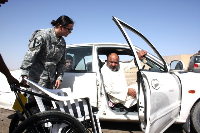 Pfc. Melissa Gonzales, a Combat Medic assigned to Co. C, 27th BSB, 4th BCT, 1st Cav. Div., presents Hussein Zabr Qaz a new wheelchair Oct. 1. Gonzales was one of two Medics who got the wheelchair from their unit to give to Hussein, who is paralyzed from the waist down.