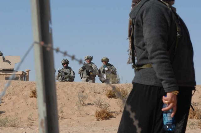 An actress portraying an Iraqi civilian stands and listens to instructions given by a unit translator over a loud speaker upon her gaining entrance to the unit's controlled entry point outside of their forward operating base located at the National Training center at Fort Irwin, Calif.