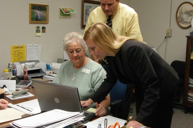 Claims Division personnel Pat Getchel (sitting), Craig Jenkins (standing) and Sherry Blount review a claim.