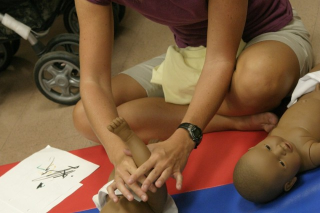 SCHOFIELD BARRACKS, Hawaii - Heather Keeler, New Parent Support home visitor, demonstrates the proper way to massage a baby using a doll. Time spent massaging a baby can heighten parent/child communication, according to Keeler.