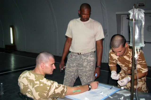 Staff Sergeant Junior St. Hilaire supervises the intravenous infusion by a Romanian Army Combat Life Saver graduate at CPB Adder.