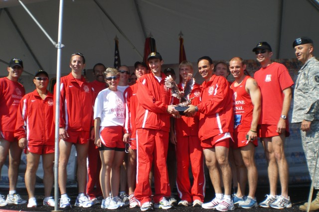Members of RedstoneAca,!a,,cs running teams gather onstage to accept the trophy for the government agency category at the 24th annual Army Ten-Miler.
