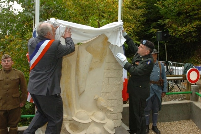 "Mayor of Binarville, France, Michel Dutier and Maj. Gen. William Terpeluk, commanding general of the 77th Regional Readiness Command, unveil the 77th ""Liberty"" Division's Lost Battalion memorial monument Oct. 7."