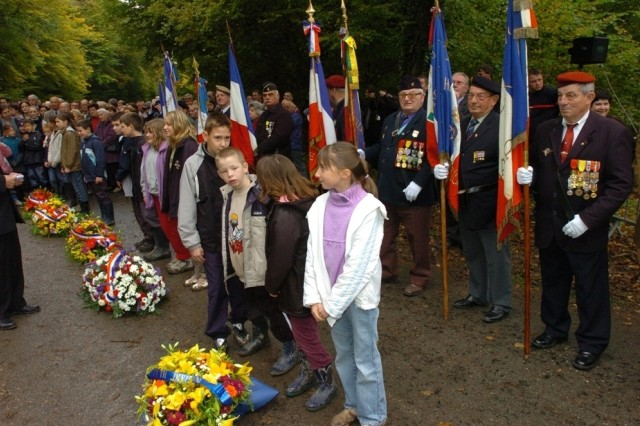 "French elementary school children from the local area stand ready to assist with the laying of wreaths at the 77th ""Liberty"" Division's Lost Battalion memorial monument ceremony. The monument was dedicated to American Soldiers who lost their lives while fighting in the Argonne forests of France exactly 90 years earlier."