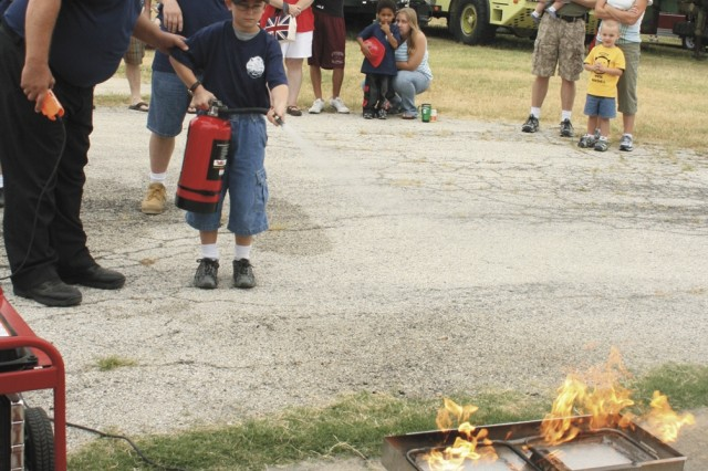 Fire Inspector Scott Rath shows Timothy Kalvaitis Jr. how to use a fire extinguisher at the fire training facility near Leadership Field. Rath recommended getting Type K fire extinguishers for the kitchen because of their low pressure spray.