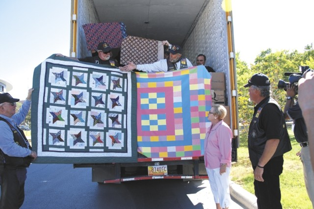 """Ed """"Wishbone"""" Summerall, New Mexico state chairman for Operation Wounded Warrior, holds up two of the many quilts donated by the Enchanted Quilters Guild of Alamogordo, N.M., to Warriors in Transition as a way of saying """"thank you for what you do for our country.""""  Judith Markelz, director of the Warrior and Family Support Center, looks at the truckload of dry goods, worth more than $35,000, brought to the center by the American Legion Riders from the Southwestern state chapters."""