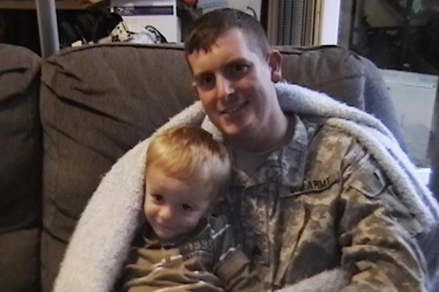 Sgt. Robert Durbin wraps his award-winning afghan around his son, Darrian.
