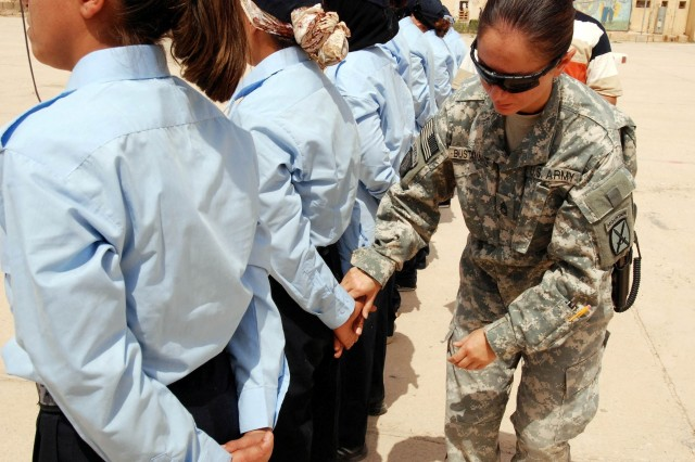 Sgt. 1st Class Sumalee Bustamante, a former drill instructor, and a military police officer with the 1st Brigade, 10th Mountain Division, corrects the hand position of a female Iraqi Police recruit at 'parade rest' during the first day of training at the Kirkuk Police Academy, Aug. 16. Bustamante and Spc. Jennifer Swierk, both MPs will assist with the training of thirty-seven females who are currently undergoing the four week training course in northeastern Iraq. (U.S. Army photo by Staff Sgt. Margaret C. Nelson, 1BCT, 10th Mtn. Div., PAO)
