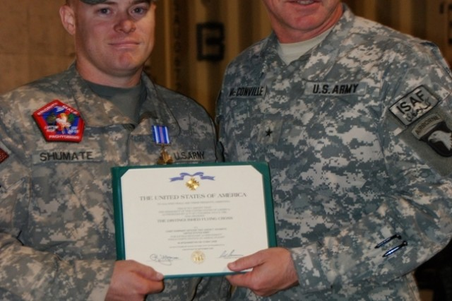 Chief Warrant Officer 2 Jason Shumate holds his award certificate with Brig. Gen. James McConville, Combined Joint Task Force-101 deputy commanding general-support and Regional Command-East. Shumate was awarded the Distinguished Flying Cross for his actions as the pilot in command of a CH-47 which came under enemy fire in May.