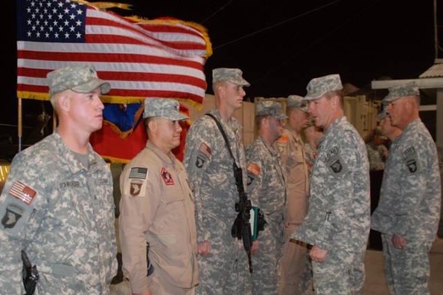 Brig. Gen. James McConville, Combined Joint Task Force-101 deputy commanding general-support and Regional Command-East and Col. James Richardson, speak to Soldiers who were awarded the Distinguished Flying Cross and Air Medals during an evening award ceremony at Bagram Air Field, Afghanistan.