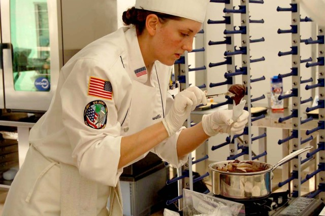 Spc. Michelle Carville, Office of the Administrative Assistant to the Secretary of the Army, Pentagon Washington D.C., fills a dispenser with chocolate for plate decoration. Carville has been a member of the U.S. Army Culinary Arts Team since March of the 2007 and is currently competing against 13 foreign military teams during the World Culinary Olympics, Oct. 19 - 22, in Erfurt, Germany.