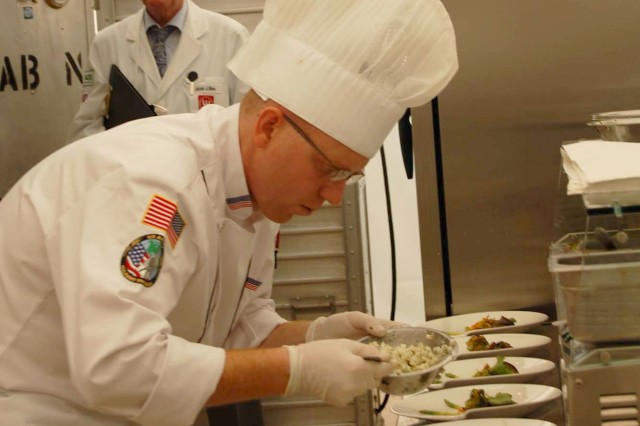 Sgt. Matthew Flemister, HQ USAG Fort Myer, is busy plating food during the Hot Kitchen Competition. Flemister has been a U.S. Army Culinary Arts Team member since 2004 and is currently competing with the team against 13 foreign military teams during the World Culinary Olympics, Oct. 19 - 22, in Erfurt, Germany. Photo by Sarah Trier, Fort Lee Public Affairs