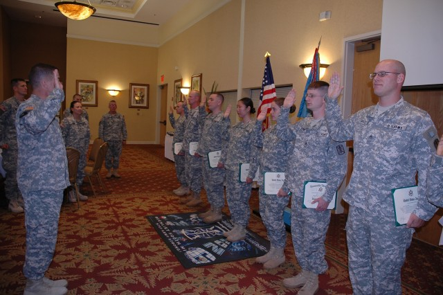 Col. Christopher Ballard, commander of the 500th Military Intelligence Brigade, recites the Oath of Reenlistment to eight Soldiers at the Brigade's Retention Award Ceremony, October 7 at the Nehelani Banquet room. This year was the first time in the Brigade's history that it met its overall retention mission.