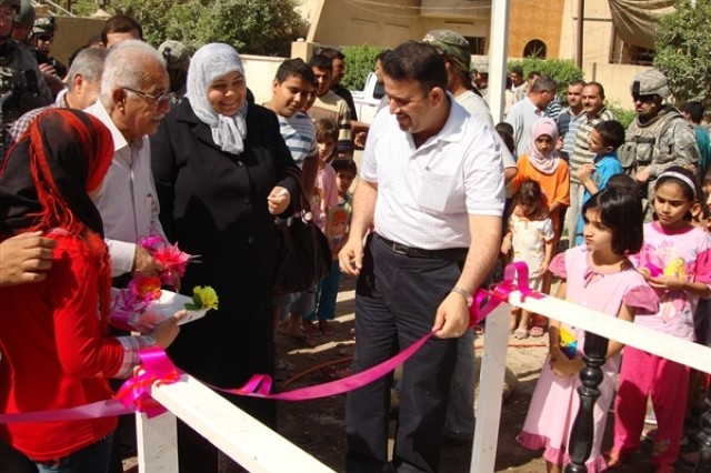 Mohammed al-Rubeiy, right, district council chief for eastern Baghdad's Karadah district, prepares to cut a ribbon for a new micro-power generator Oct. 17, 2008. The generator will provide constant power to more than 300 homes in the area.