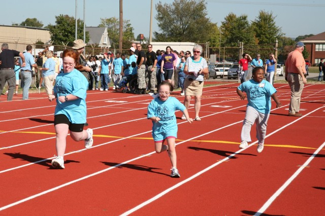 A group of employees from SMDC/ARSTRAT volunteered to assist with the 41st Special Olympics at Milton Frank Stadium in Huntsville, Ala., Oct. 14.    More than 350 Madison County special needs athletes competed in events such as a 50-meter run, a long jump, a softball throw, and other track and field events.    Each competitor was teamed with at least one escort to make sure the athlete made it to his or her scheduled event on time.  The escorts also cheered for their athletes and gave hugs or high-fives upon completion of events.    Every athlete was recognized by taking their place on the winners' platform and receiving a ribbon for their accomplishments.