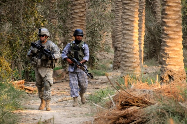 Army Staff Sgt. Kelley Martin, left, a tank commander with the 4th Infantry Division's Company C, 2nd Combined Arms Battalion, 8th Infantry Regiment, 2nd Brigade Combat Team, walks through a date palm grove with an Iraqi police officer during a patrol in Diwaniya, Iraq, Oct. 14, 2008.