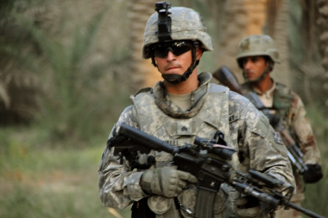 Sgt. Abel Valli, a squad leader with the 4th Infantry Division's Company C, 2nd Combined Arms Battalion, 8th Infantry Regiment, 2nd Brigade Combat Team, along with an Iraqi soldier, scans for anything suspicious during a patrol in a date palm grove in Diwaniya, Iraq, Oct. 14, 2008.