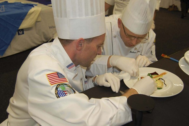 U.S. Army Culinary Arts Team competitors Senior Chief Petty Officer Justin Reed and Sgt. Matthew Flemister perfect their work after spending 24 hours in the kitchen. The cold food display event  was staged at the Messe Convention Center Oct. 22 and was the second event at the World Culinary Olympics in Erfurt, Germany, where culinary masters from 50 nations competed for medals. Photo by Sarah Trier, Fort Lee Public Affairs