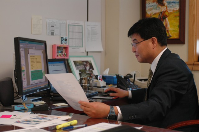 Ko, Un Yong, the budget officer for 2ID Resource Management Office, evaluates the annual budget plan for the division at his office in Freeman Hall, Camp Red Cloud, Korea.