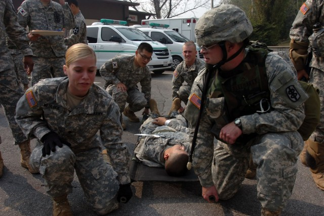 Spc. Natasha Medlock, a dental specialist for 618th Dental Co., 168 MMB, helps  transport a 'wounded' Soldier for medical help during an Area 1-wide Adaptive Focus Training Exercise at Camp Casey Oct. 16.