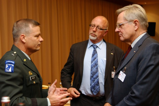 After his presentation on the Georgia humanitarian aid mission Brig. Gen. Jon Miller, deputy commanding general of U.S. Army Europe's 21st Theater Support Command (left), discusses his participation in the mission with retired German army Brig. Gen. Dr. Volker Schwamborn (center) and retired German army Lt. Gen. Ruediger Drews, at the 28th annual U.S. Army Europe Legion of Merit Conference in Heidelberg Germany, Oct. 20.
