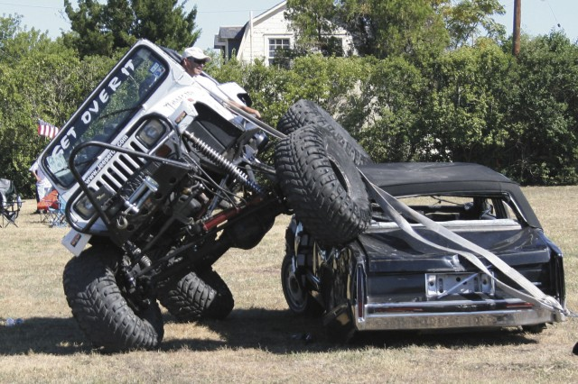"""The Midnight 4 Wheeler """"gets over"""" a Cadillac at the Car Smash event Oct. 18 at the Fall Fest, which was sponsored by Directorate of Family, Morale, Welfare and Recreation. Thousands of people attended Fall Fest, which began Oct. 17 in the"""