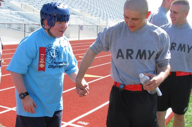Pvt. Matthew Schultz takes his charge, Special Olympics athlete Michael Richardson, by the hand to guide him off the track after his race. Michael was able to complete the 100-meter walk thanks to the encouragement of Schultz, Pvt. Kory Roberts and Pfc. Shawn Anders, all of the 832nd Ordnance Battalion. About 200 Soldiers of the 832nd chaperoned, cheered and coached athletes at the 41st annual Madison County Special Olympics Track and Field Events at Milton Frank Stadium on Oct. 14.