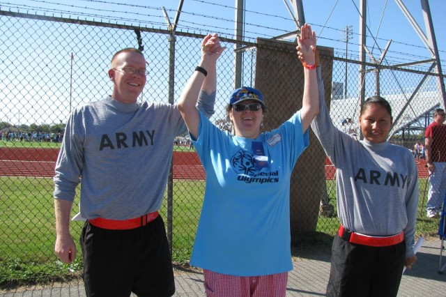 "Pvt. David Hawkins and Pvt. Rhiannon Apache celebrate with Special Olympics athlete Denise Framarin, who won the female softball throw. Aca,!A""SheAca,!a,,cs my hero,Aca,!A? Hawkins said."