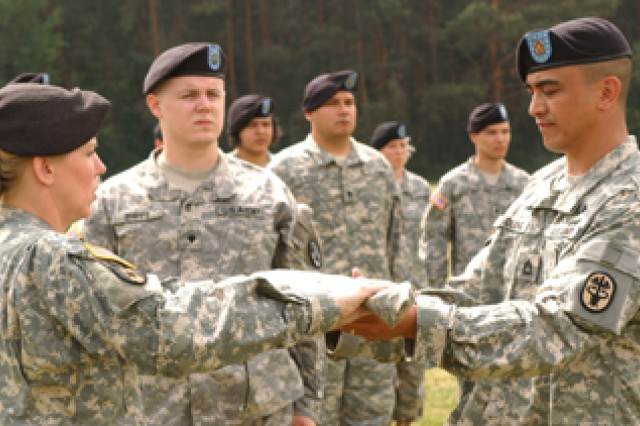 Lt. Col. Karrie Fristoe (left) returns Hanau Health Clinic's cased colors to the charge of Sgt. 1st Class Sean Tudlong while the color bearer, Spc. Stephen Phipps, looks on. The health and dental clinics at Hanau closed this summer, among a number of changes to Army medical facilities in Germany.