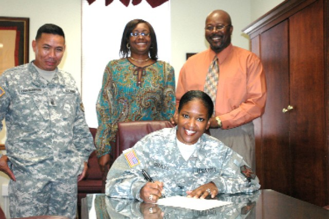 Col. Deborah B. Grays (seated), commander, U.S. Army Garrison  takes a moment to sign a proclamation declaring Thursday through Oct. 31 as Red Ribbon Week as, from left, Command Sgt. Maj. Kenny S. LeonGuerrero, garrison command sergeant major, Alcana Morris, Installation Biochemical Testing coordinator, and Moses Simmons Jr., director, Alcohol and Drug Control Office, serve as witnesses.