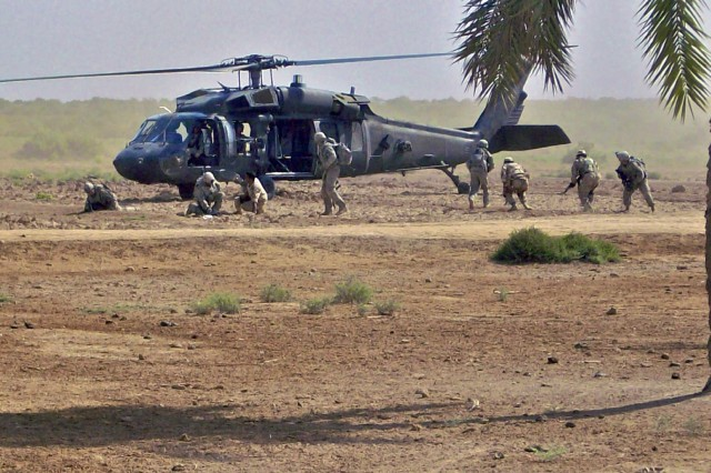 Iraqi troops assigned to the 2/38/10th IA Div. and U.S. Soldiers from the 5th Bn., 82nd FA Regt., 4th BCT, 1st Cav. Div., dismount a UH-60 Black Hawk helicopter during a daytime air assault in the vicinity of Amarah Oct. 18.
